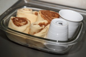 unbaked rolls with cups in dish