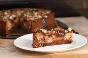 A slice of cheesecake - chocolate chip cookie crust, with chocolate, nuts and caramel filling
