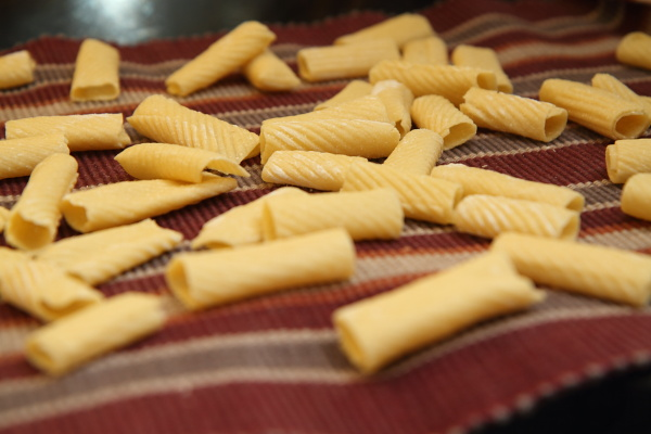 hand rolled rigatoni drying on a towel